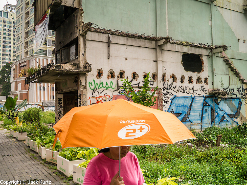 16 OCTOBER 2012 - BANGKOK, THAILAND: A woman under an umbrella walks past abandoned building on Phetchaburi Rd in central Bangkok, Thailand. The building sits in an empty lot next to an exclusive high rise condominium building. It used to be an optician's shop with residences above the ground floor shop. The global economic slowdown had little visible effect in Bangkok. Construction projects dot the city of 12 million and development continues unabated.    PHOTO BY JACK KURTZ