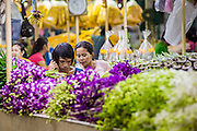 09 OCTOBER 2012 - BANGKOK, THAILAND:  Vendors in their booth in the Bangkok Flower Market. The Bangkok Flower Market (Pak Klong Talad) is the biggest wholesale and retail fresh flower market in Bangkok. It is also one of the largest fresh fruit and produce markets in the city. The market is located in the old part of the city, south of Wat Po (Temple of the Reclining Buddha) and the Grand Palace.    PHOTO BY JACK KURTZ