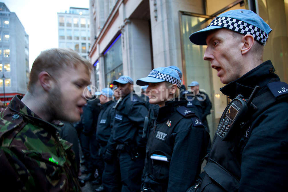 Anti-capitalist protesters argues with a policeman he accused of punching a woman outside Panton House on Panton Street. They were targeting Mick Davis, CEO of mining company Xstrata, which has offices in the building and is one of the highest paid from FTSE 100 companies.