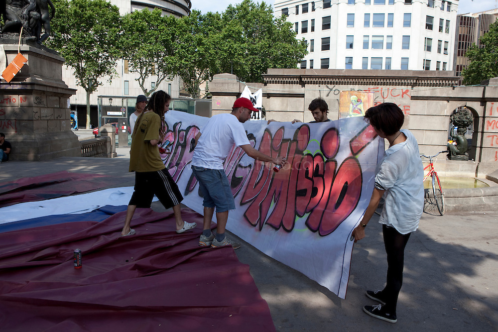 Antigovernment protesters spray paint a banner at the Spanish revolution camp at Placa de Catalunya, Barcelona, Spain. The square has been relatively quiet since police attacked and beat protestors on May 27 2011.