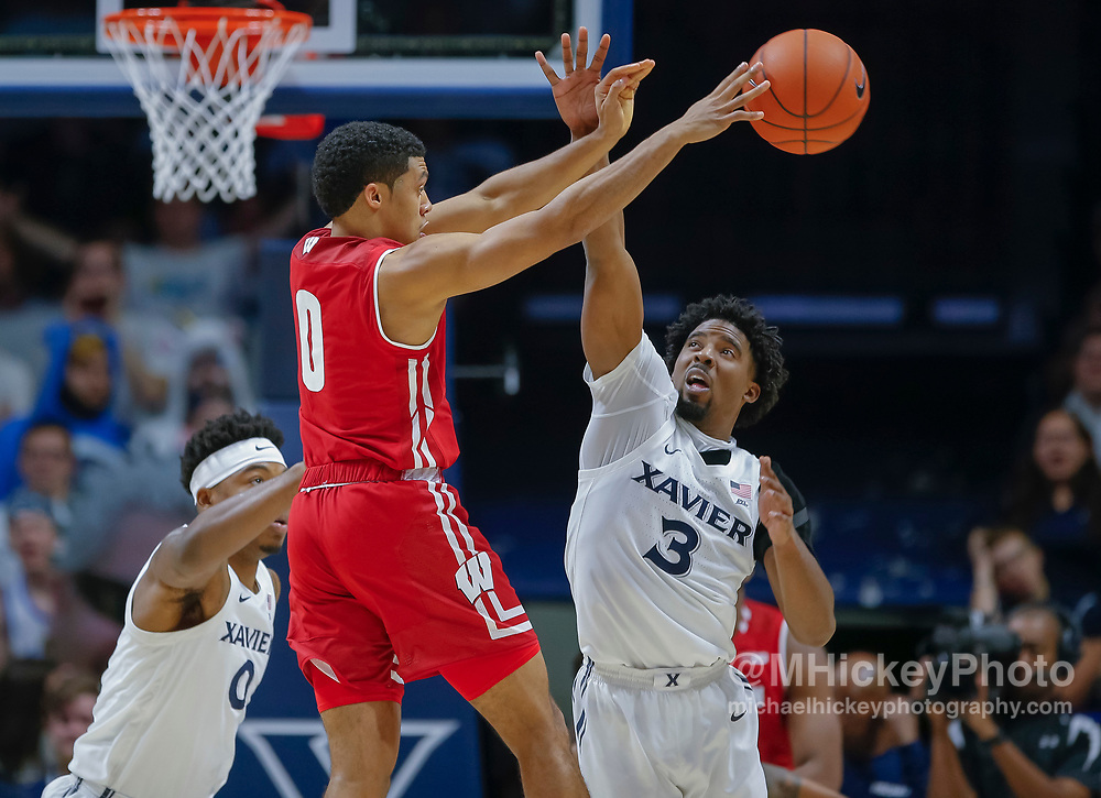 CINCINNATI, OH - NOVEMBER 13: D'Mitrik Trice #0 of the Wisconsin Badgers passes the ball off as Quentin Goodin #3 of the Xavier Musketeers defends at Cintas Center on November 13, 2018 in Cincinnati, Ohio. (Photo by Michael Hickey/Getty Images) *** Local Caption *** D'Mitrik Trice