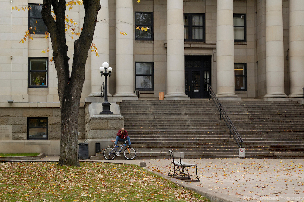 Person sitting on courthouse steps in the fall, Prescott, Arizona