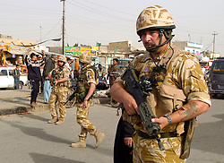 Soldiers from the East and West Riding Regiment, Territorial Army, wearing desert camouflage, Kevlar helmets and body armor, carrying SA80 assault rifles which are fitted with SUSAT sights on foot patrol through the streets of Basra during Op Telic in March 2005