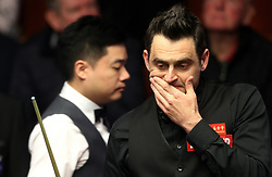 Ronnie O'Sullivan reacts after a missed shot against Ding Junhui (left), on day twelve of the Betfred Snooker World Championships at the Crucible Theatre, Sheffield.