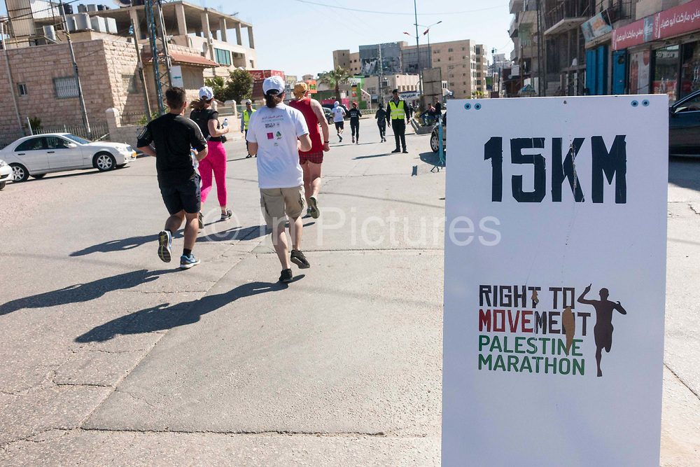 A marker post shows 15kms during the Right to Movement, Palestine Marathon on 1st April 2016 in Bethlehem, West Bank. During the Palestine Marathon, thousands of runners, both professional and amateur come from across the globe to take part in the Right to Movement event.