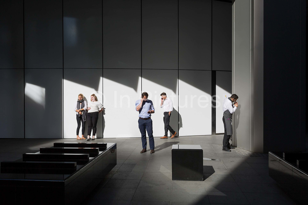 Office workers enjoy the warmth of autumnal sunshine outside the Willis Towers Watson building on Fenchurch Avenue in the heart of the capitals financial district aka The Square Mile, on 24th September 2018, in London, England.