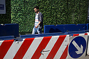 Man wearing a t-shirt matching the scene walks past a barrier made of concrete and painted with red and white stripes and hoarding made to look like a large hedge of leaves, outside a construction site at Smithfields in London, UK.