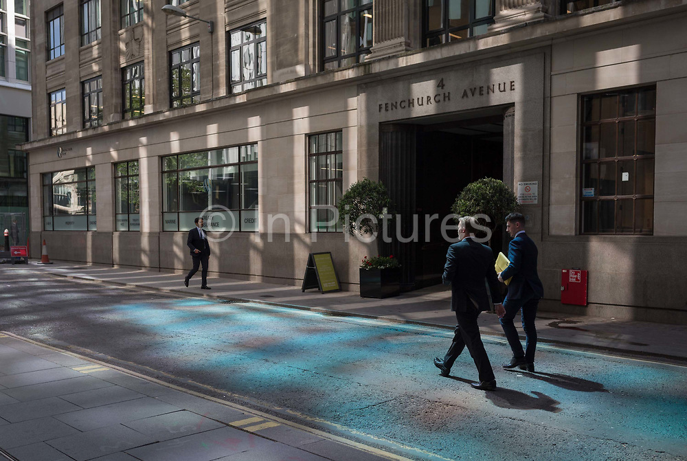 Financial services business people walk through reflected light from a nearby skyscraper in the City of London, the capitals financial district aka the Square Mile, on 17th May 2018, in London, UK.