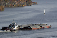 Fort Montgomery, NY - A tugboat pushes barges down the Hudson River just south of the Bear Mountain Bridge  on Nov. 2, 2008. A sailboat is also heading south on the river in the background.