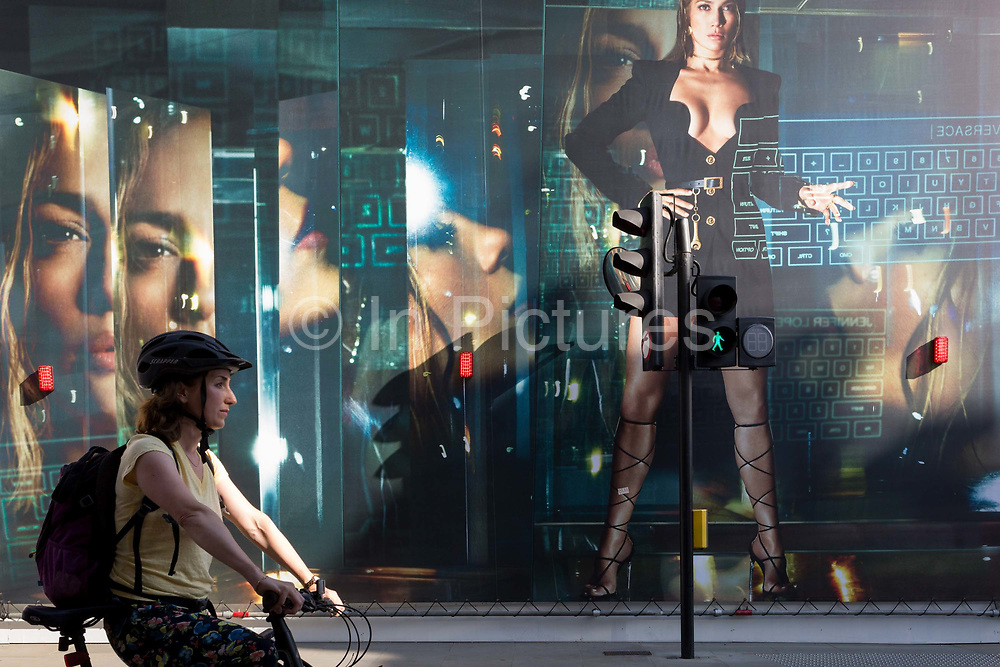 With a further 184 reported UK Covid deaths in the last 24 hrs, a total now of 43,414, a lady cyclist stops at a red light infront of a billboard during the construction of a new Versace store on New Bond Street during the Covid pandemic lockdown, now easing after three months of the Stay At Home policy but now being relaxed as the shops re-open, on 26th June 2020, in London, England. Government restrictions on the 2 metre rule is to be realxed on 4th July and replaced with one metre plus in the hope it stimulates the struggling UK economy.