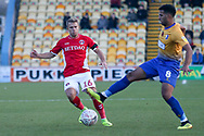 Jamie Ward of Charlton Athletic (16) is tackled by Jacob Mellis of Mansfield Town (8) during the The FA Cup match between Mansfield Town and Charlton Athletic at the One Call Stadium, Mansfield, England on 11 November 2018.