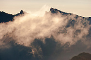 A cloud rises from the Catt Creek valley past the Sawtooth Ridge and its fire lookout on the peak of High Rock in the Gifford Pinchot National Forest of the Cascade Mountain Range in Washington, USA. (viewed from the High Hut ridge in the Tahoma State Forest)