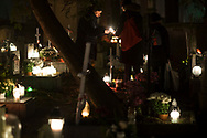 People light a candle at Rakowicki cemetery in Krakow, Poland 2019.