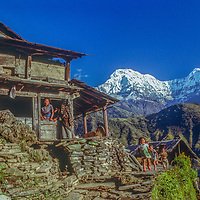 Children run past their family's farm in Gandrung, Nepal.  Annapurna South rises in the background.