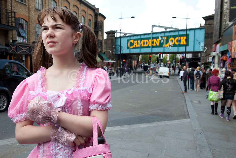Georgia (11, wearing a pink Lolita dress) spending a day out in Camden Town, North London. Here they are walking near to the famous sign for Camden Lock on the railway bridge. Louise (her mother) is on various benefits to help support her family income, and housing, although recent government changes to benefits may affect her family drastically, possibly meaning they may have to move out of London. Louise Ryan was born on the Wirral peninsula in 1970.  She moved to London with her family in 1980.  Having lived in both Manchester and Ireland, she now lives permanently in North London with her husband and two children. Through the years Louise has battled to recover from a serious motorcycle accident in 1992 and has recently been diagnosed with Bipolar Affective Disorder. (Photo by Mike Kemp/For The Washington Post)