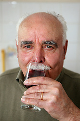 Grandfather at home drinking red wine,