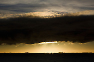 A low bank of dark and stormy cloud obscures the sun, as it nears its evening nadir while crossing the Antarctic Circle near Adelaide Island, Antarctica