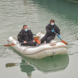 © Licensed to London News Pictures. 14/09/2021. Dover, UK. Border Force officers row a dinghy used by migrants at Dover Harbour in Kent. Migrants are continuing to attempt the crossing from France as the weather worsens. Photo credit: Stuart Brock/LNP