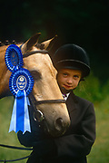 Portrait of a young girl holding her First Prize winning pony at a gymkhana meeting, on 2nd July 1995, in Cheltenham, Gloucestershire, England. Gymkhana is an Indian Raj term which originally referred to a place where sporting events took place and referred to any of various meets at which contests were held to test the skill of the competitors. In the United Kingdom and east coast of the United States, the term gymkhana now almost always refers to an equestrian event for riders on horses, often with the emphasis on childrens participation such as those organised here by the Pony Club. Gymkhana classes include timed speed events such as barrel racing, keyhole, keg race also known as down and back, flag race, and pole bending.