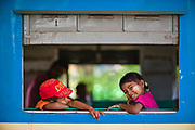 A young brother and sister lean through an open carriage window. The girl's face has had a decorative circle of thanaka paste applied, Central Railway Station, Yangon, Myanmar