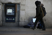 Homeless people in the United Kingdom facing the risk of death from Coronavirus. Last years alone, 320,000 people were recorded as homeless in Britain, analysis from housing charity Shelter suggests. It is a rise of 13,000, or 4%, on last year's figures and equivalent to 36 new people becoming homeless every day.<br /> In this picture, a homeless man is seating at the Borough Market while a pedestrian passes by on Sunday, March 22, 2020. For most people, the new coronavirus causes only mild or moderate symptoms, such as fever and cough. For some, especially older adults and people with existing health problems, it can cause more severe illness, including pneumonia. <br /> (Photo/Vudi Xhymshiti)