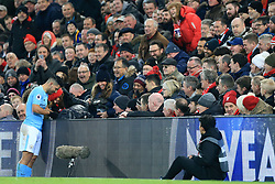 14 January 2018 - Premier League Football - Liverpool v Manchester City - Fans watch as Sergio Aguero of Man City helps an eager young fan retrieve the ball from behind the advertising boards - Photo: Simon Stacpoole / Offside