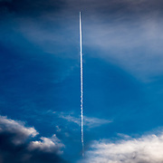 I took this picture by chance while looking at the sky. A woman to whom I showed the shot revealed me the depth behind: It is all about reaching verticality, symbolized by the jet smoke trail dividing the picture in two. On the horizontal level, on the left, dark clouds, our dark side. On the right, white and bright clouds, and you, in the middle, neither on the left or the right, just straight up aligned into verticality.