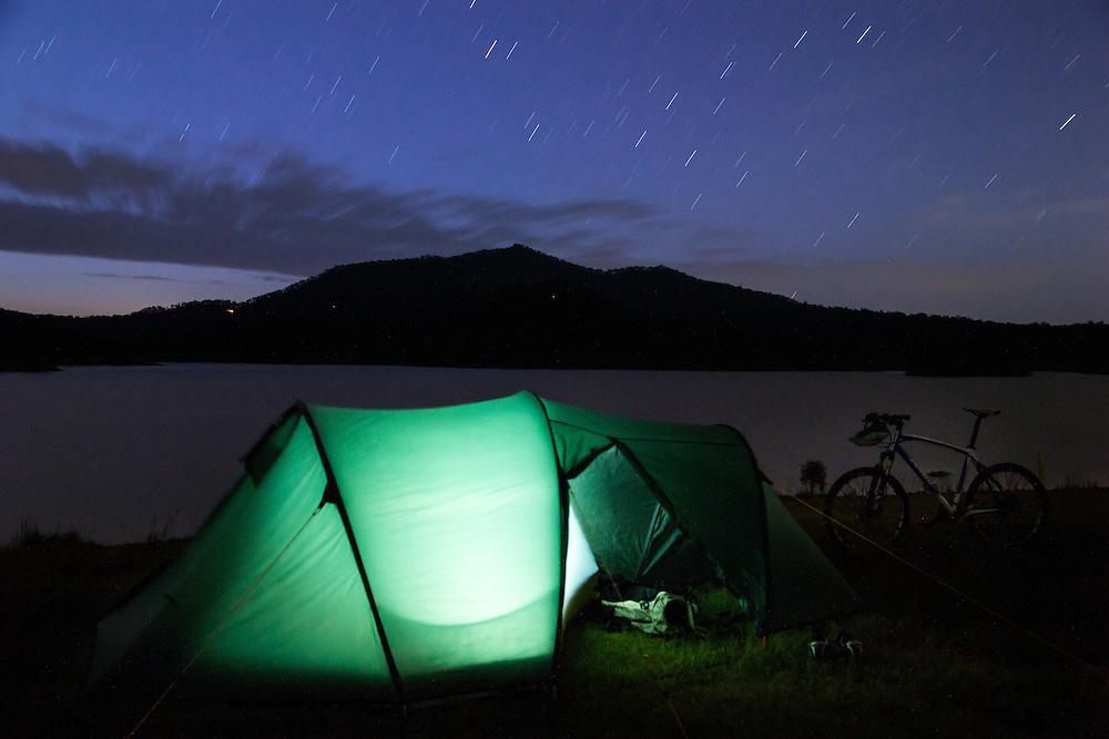 A tent lit up alongside Wyaralong Dam at Mt Joyce.