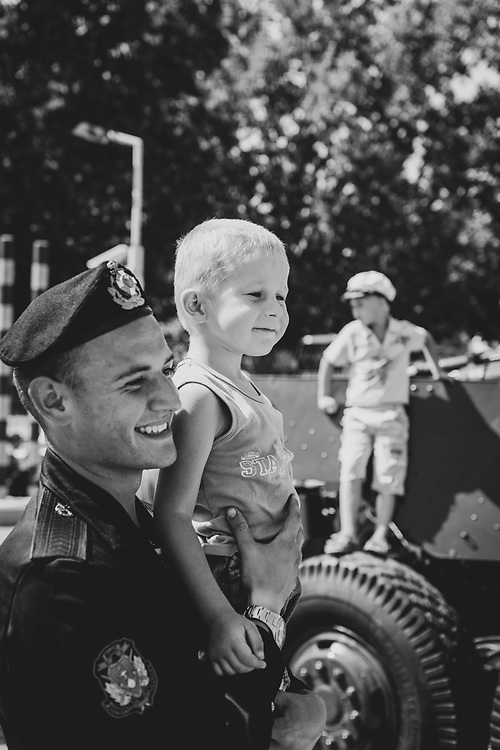 Sevastopol, Crimea, Ukraine - July 28, 2013: A Ukrainian sailor poses for a photo with someone's child during Sevastopol's annual Navy Day.