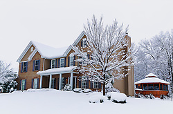 A view from the front corner of the house, highlighting or snowy gazebo in the back