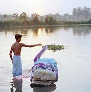 Indian man washing clothes in Gomti River, Lucknow, Uttar Pradesh, India