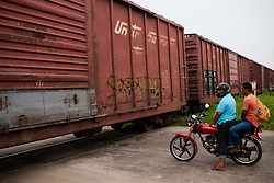 People wait as a freight train heads south through Tenosique, Tabasco.  Central American migrants ride on similar trains headed north from Tenosique as they try to make their way to the United States.  The trip for these migrants has become increasingly dangerous over the past several years as Mexico's drug war has raged and kidnappings and killings of migrants has increased.