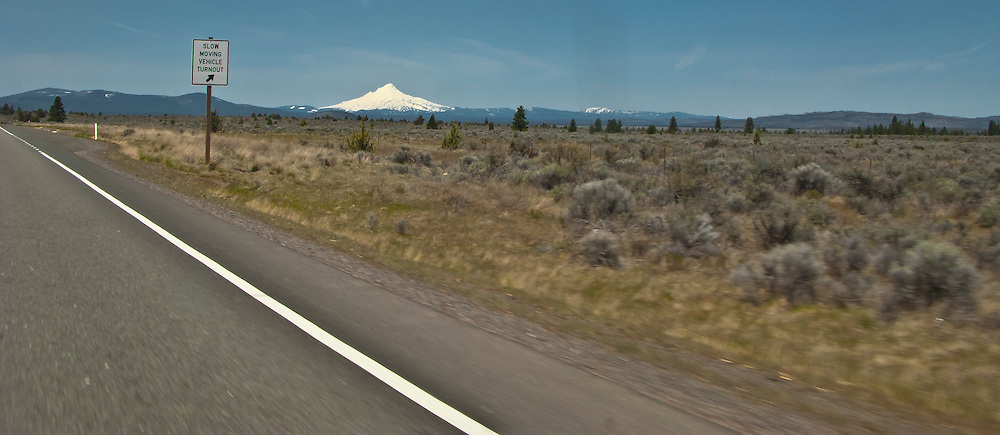 scene along a cross country trip with in a classic Mini Cooper auto - slow moving vehicle turnout sign along US 26 with a distant view of Mt Hood