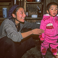 A Sherpa mother dresses her son in her kitchen in Namche Bazaar, the leading Sherpa city of Nepal's Himalaya.