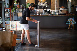 © Licensed to London News Pictures . 20/05/2020 . Manchester , UK . A customer uses a foot operated hand sanitiser dispenser in the doorway of Ezra & Gil coffee shop in Manchester City Centre . On the hottest day of the year so far independently run coffee shops and bars are open and trading with social distancing measures applied , after a period of being shut in an effort to reduce the spread of Covid-19 . Photo credit : Joel Goodman/LNP