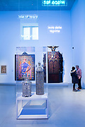 Two Torah cases in the foreround; in the background, Alios Itzhak, from the series The World Stage: Israel, by Kehinde Wiley, 2011 and a Torah ark from the Adath Yeshurum synagogue, by Abraham Shulkin, ca. 1899.