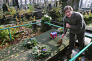 A man sweeps a grave preparing for All Saints Day. Powazek Cemetery. Warsaw, Poland. Andrej W. Wernik sweeps his parents' graves.