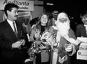 5,000,000th Passenger Through Dublin Airport. (T12).1989..22.12.1989..12.22.1989..22nd December 1989..The date,Friday,22nd December 1989 will be remembered as an historic day in Irish Aviation as Aer Rianta celebrated the 5millionth passenger to fly through Dublin Airport in one year. The Lucky passenger, Nicola Wynne, arrived at 10AM from Germany and was welcomed to Dublin Airport by General Manager,Tom Cullen...Picture shows Santa and Mr Terence McGowan,Delta Airlines sharing the champagne with Nicola Wynne after she was declared the 5millionth traveller of the year.