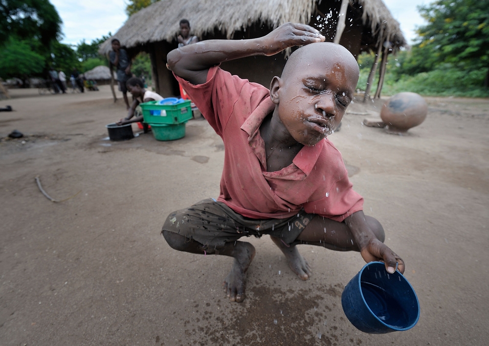 """Mission Dzongololo, 10, washes his face as he prepares to go to school in the morning in Chidyamanga, a village in southern Malawi that has been hard hit by drought in recent years, leading to chronic food insecurity, especially during the """"hunger season,"""" when farmers are waiting for the harvest."""