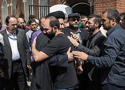 © Licensed to London News Pictures. 14/07/2017. London, UK. Mourners look on as brothers Bashir (R) and Hamid Jafari are comforted after they carried the coffin of their father Mr Ali Jafari from the Hussaini Islamic Mission after funeral prayers. Mr Jafari, 82, was killed in the fire that destroyed Grenfell Tower in June. Photo credit: Peter Macdiarmid/LNP