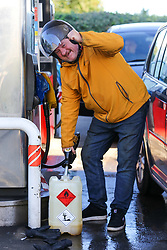 © Licensed to London News Pictures. 29/09/2021. London, UK. A man gesturers as he fills a large container at Texaco petrol station in north London on the sixth day of the fuel crisis, amid fears of fuel running out due to a shortage of HGV drivers. According to the government, 75 army tanker drivers have been put on standby to deliver motor fuel in order to ease the chaos at petrol stations. Photo credit: Dinendra Haria/LNP