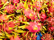 25 JUNE 2011 - SANPATONG, THAILAND: Thai dragon fruit for sale at the Sanpatong buffalo market near Chiang Mai, Thailand, June 25. The buffalo market in Sanpatong started as a weekly gathering of farmers and traders buying and selling water buffalo, the iconic beast of burden in Southeast Asia, more than 60 years ago and has grown into one of the largest weekend markets in northern Thailand. Buffalo and cattle are still a main focus of the market, but traders also buy and sell fighting cocks, food, clothes, home brew and patent medicines.    PHOTO BY JACK KURTZ