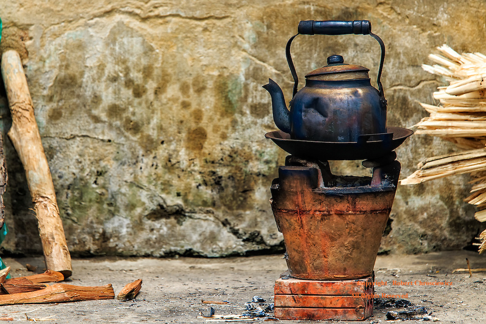 Blackened Kettle: A blackened kettle is left perched on a heating pan over-top of a charcoal filled vessel, street-side in Hoi An Vietnam.
