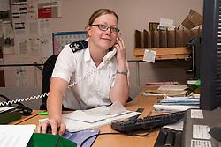 Female Prison Officer in the office, UK prison