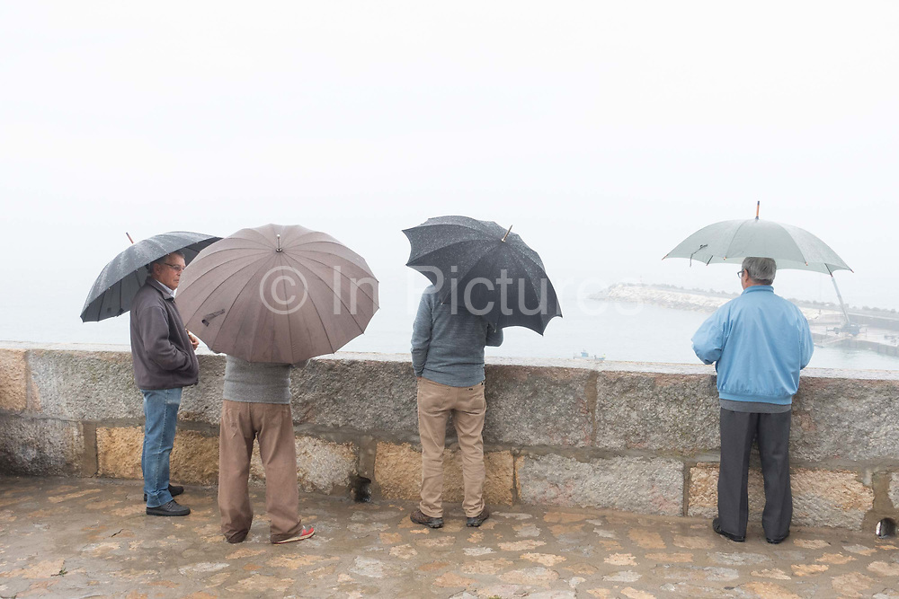 Four Portuguese men with umbrellas looking out to sea at Fisherman's Beach on 25th May 2018 in Ericeira in Portugal. Ericeira is a civil parish and seaside resort/fishing community on the western coast of Portugal.