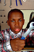 Kid age 12 working with wrench at inner city bicycle repair shop.  St Paul  Minnesota USA