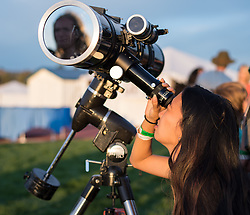 An attendee of the star party looks through a telescope at the sun the night before crowds come to watch the total solar eclipse in Madras, Oregon on Sunday, August 20, 2017. The eclipse will be sweeping across a narrow portion of the contiguous United States from Lincoln Beach, Oregon to Charleston, South Carolina on August 21. A partial solar eclipse will be visible across the entire North American continent along with parts of South America, Africa, and Europe.  Photo Credit: (NASA/Aubrey Gemignani)