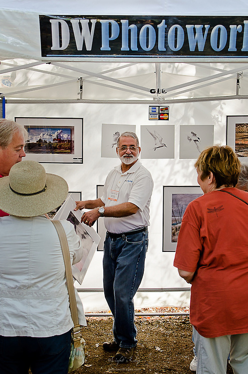 Dave Woeller, owner of DWPhotoworks discusses aspects of his images with patrons at the 2012 Wheaton Arts Fine Craft Festival.