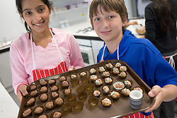 Two students showing a tray of sweets they have made in Food Studies during their induction day,