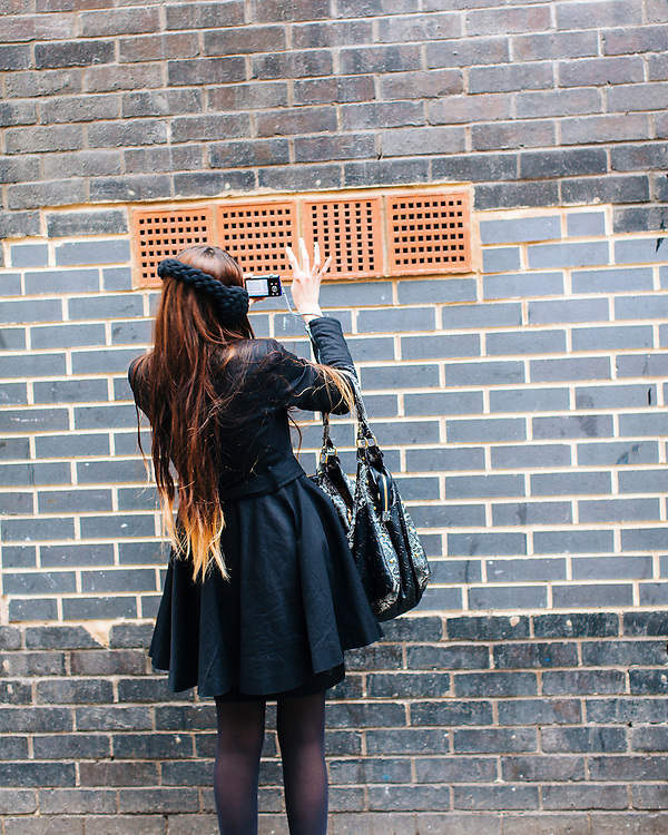 Female seen from behind using mobile phone to take photographs